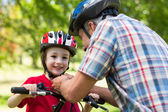Father attaching his sons cycling helmet — Stock Photo