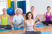 Class practicing yoga with instructor at gym — Stock Photo