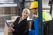 Warehouse manager talking with forklift driver — Stock Photo