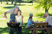 Happy father doing barbecue with his daughter — Stock Photo