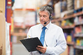 Warehouse manager wearing headset writing on clipboard — Stock fotografie