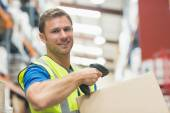 Smiling manual worker scanning package — Stock Photo