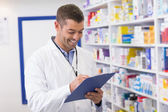 Smiling pharmacist writing on clipboard — Stock Photo