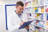 Smiling pharmacist writing on clipboard — Stock fotografie
