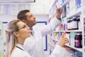 Team of pharmacists looking at medicine — Stock Photo