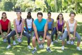Fitness group squatting in park with kettle bells  — Stock Photo