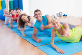 People on exercise mats gesturing thumbs up at gym — Stock Photo