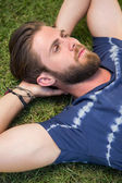 Handsome hipster lying on grass — Stock Photo