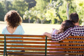 Lonely woman sitting with couple in park — Stock Photo