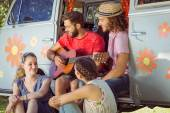 Hipster friends sitting by camper van — Stock Photo