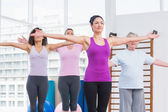 Friends with arms outstretched exercising in gym — Foto de Stock