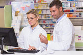 Team of pharmacists looking at the computer — Stock Photo