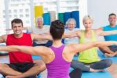 People practicing yoga in health club — Stock Photo