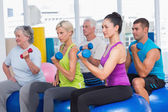 People working out with dumbbells in gym class — ストック写真