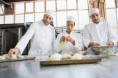 Concentrated colleagues kneading uncooked dough — Stock Photo