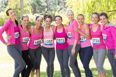 Smiling women running for breast cancer awareness — Stock Photo