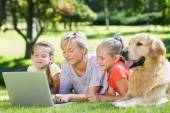 Happy family using laptop in the park — Stock Photo