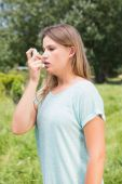 Pretty blonde using an asthma inhaler — Stock Photo