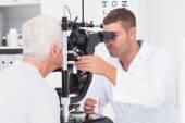Optometrist examining senior mans eyes — Stock Photo