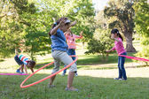 Friends playing with hula hoops in park — Stock Photo