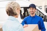 Delivery driver passing parcel to customer — Stock Photo