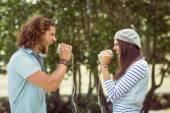 Young couple shouting through tin cans — Stock Photo