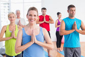 People meditating with hands joined in yoga class — Stock Photo