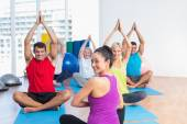 Instructor with class practicing yoga in fitness studio — Stock Photo