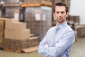 Manager with arms crossed in warehouse — Stock Photo