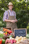 Farmer selling organic veg at market — Stock Photo