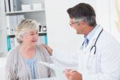 Doctor consoling senior woman in clinic — Stock Photo