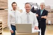 Warehouse team working together on laptop — Foto Stock
