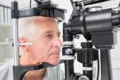 Man looking into slit lamp — Stock Photo