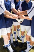 Pretty football players putting hands together  — Stock Photo