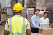 Warehouse worker in front of his managers — Stock Photo