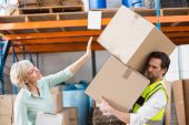 Worker balancing heavy cardboard boxes — Stock Photo