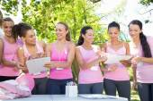 Smiling women organising event for breast cancer awareness — Stock Photo