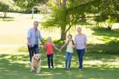 Family walking in park with dog — Stock Photo
