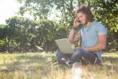 Young man using laptop in park — Stock Photo