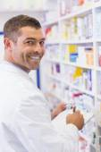 Happy pharmacist writing on clipboard — Stock Photo