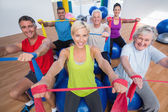 Happy people exercising with resistance bands in gym class — Stok fotoğraf