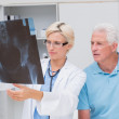 Doctor and senior patient examining x-ray — Stock Photo #69020843