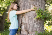 Pretty blonde hugging a tree — Stock Photo
