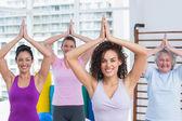 Happy friends practicing tree pose in fitness studio — Stock Photo