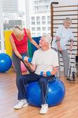 Trainer assisting senior man in lifting dumbbells — Stock Photo