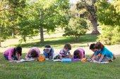 Crianças em idade escolar fazendo lição de casa na grama — Fotografia Stock
