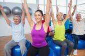 People sitting on exercise balls with hands raised — Stock Photo