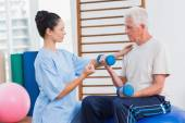Trainer assisting man in lifting dumbbells — Stock Photo