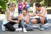 Woman with injured knee during race in park — Stock Photo