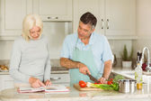 Mature couple following vegetarian recipe — Stock Photo